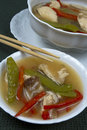 Bowl and tureen of asian chicken soup with red pepper snow peas on green linens with chopsticks Stock Photography