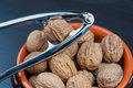 Bowl of walnuts and nutcracker on wooden table Royalty Free Stock Photo