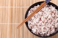 Bowl of white rice and quinoa with chopsticks on bamboo mat. Royalty Free Stock Photo