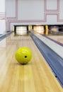 Bowling ball rolling toward pins yellow Royalty Free Stock Photography