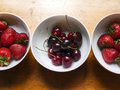 Bowls of cherries and strawberries on wooden table Stock Images