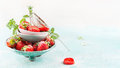 Bowls with fresh strawberries and sugar strainer on light blue background side view banner Royalty Free Stock Photo