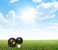 Bowls on lawn a set of wooden next to a jack a perfect flat green against a blue sky with white clouds Royalty Free Stock Photography