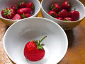 Bowls of strawberries on wooden table three a Royalty Free Stock Photos
