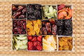 Box with assortment of dried fruits closeup on beige mat background. Royalty Free Stock Photo