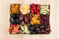 Box with assortment of dried fruits closeup on beige wooden background. Royalty Free Stock Photo