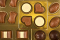 Box of chocolates golden with different shapes colors and flavors Stock Image