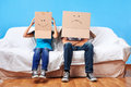 Box face couple sitting on couch with moving boxes on head having fun together Royalty Free Stock Photo