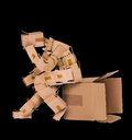 Box man deep thinker thinking and sat on a on a black background Stock Photos