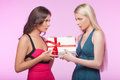 This box is mine it� two angry young women trying to take away one gift while isolated on pink background Stock Image