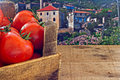 Box of red ripe tomatoes with countryside background old Royalty Free Stock Photo