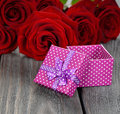Box and red roses on a gray background Royalty Free Stock Images