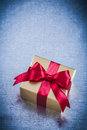 Boxed golden present with red ribbon on metallic background Stock Photography