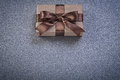 Boxed present in brown wrapping paper on grey background directl directly above celebrations concept Royalty Free Stock Image