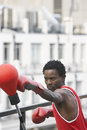 Boxer punching punchball outdoors young african american against building Royalty Free Stock Images
