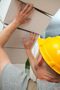 Boxes falling on worker white and heavy with yellow helmet Stock Image