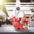 Boxing day. Shopping basket with gifts in supermarket Royalty Free Stock Photo