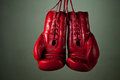Boxing gloves hanging from laces on a grey background Stock Photos