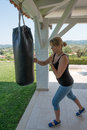 Boxing young female using a punch bag Stock Photo
