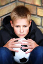 A boy against a wall with a ball Royalty Free Stock Photo