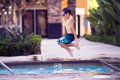 Boy in the air, jumping in a pool Royalty Free Stock Photo