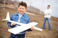 Boy with airplane photo of happy kid toy looking at camera his father on background Stock Image