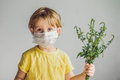 The boy is allergic to ragweed. In a medical mask, he holds a ra Royalty Free Stock Photo