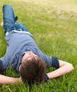 Boy alone lying on green grass Stock Image