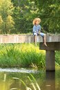 Boy during angling with rod on bridge Royalty Free Stock Photo