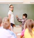 Boy answers questions of teachers near a school board Royalty Free Stock Photo