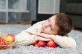 Boy with apples lies on the carpet at home smiling Stock Photos