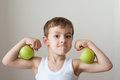 Boy with apples show biceps Royalty Free Stock Photo