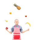 A boy with apron juggling with fruits isolated on white background Royalty Free Stock Photo