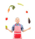 A boy with apron juggling with vegetables isolated on white background Stock Photo