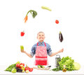 A boy with apron juggling with vegetables while preparing salad isolated on white background Stock Photography