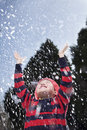 Boy with arms raised feeling the snow Stock Photo