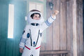 Boy in astronaut costume flying on porch