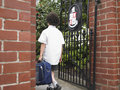 Boy with backpack entering school gate rear view of young Stock Photos