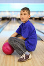 Boy with ball sits on floor in bowling Royalty Free Stock Photo