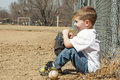 Boy with baseball and glove young sits against the dugout fence on a ball field his ball Stock Photos