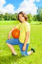 Boy with basketball posing portrait of years old sit on squads ball on the field on bright sunny day Royalty Free Stock Image