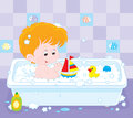Boy bathing little playing with toys in a bath with foam Stock Image