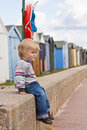 Boy by beach huts Stock Images