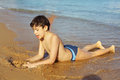 Boy on the beach take sun bathing play with sand Royalty Free Stock Photo