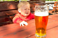 Boy and beer little crying seeing a glass of Royalty Free Stock Images
