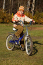 Boy on bicycle in autumn park on sunny day Royalty Free Stock Image
