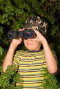 Boy with binoculars school aged looks through a juniper tree in the background Royalty Free Stock Photos