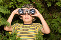 Boy with binoculars school aged looks through a juniper tree in the background Royalty Free Stock Image