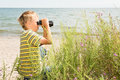 Boy with binoculars a school aged looks through a sea shore on the background Stock Images