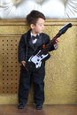 Boy in black tuxedo stands with guitar a little near a wall a Stock Images